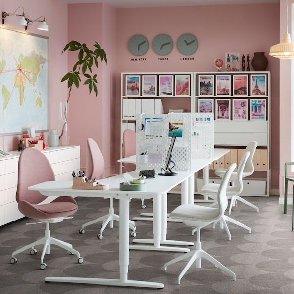 An office setting with white desks and pink and white chairs, a world map on the wall, shelving and storage.