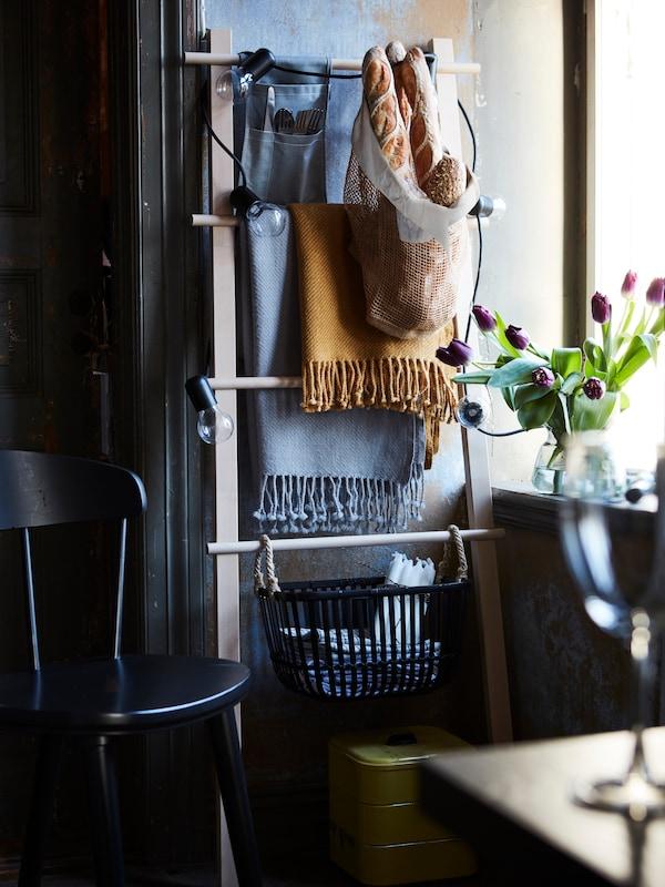 Na zidu stoji stalak za ručnike i služi kao dodatno rješenje za odlaganje. Na njemu vise lagane deke i košare.