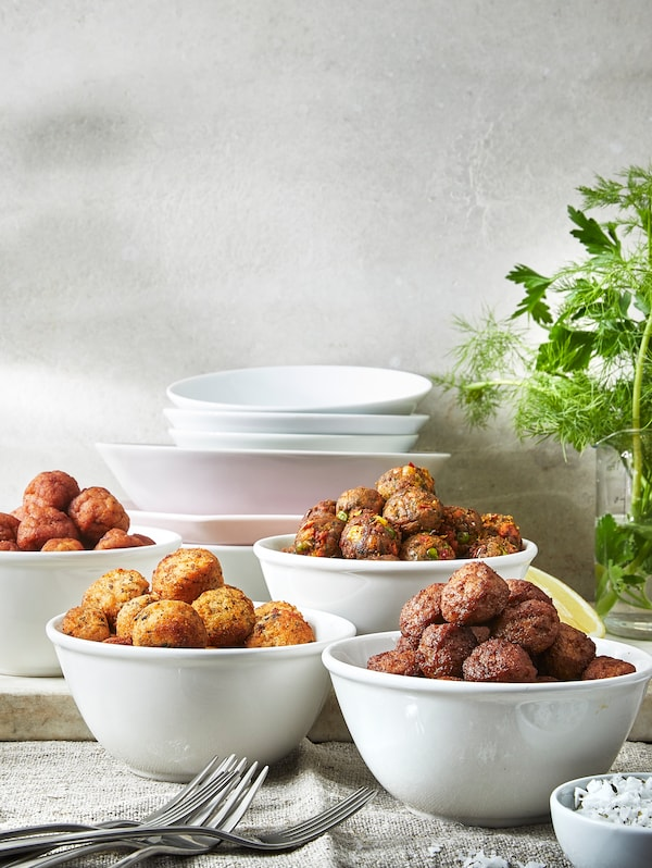 A table with four white bowls containing HUVUDROLL chicken meatballs, veggie balls, meatballs and salmon and cod balls.