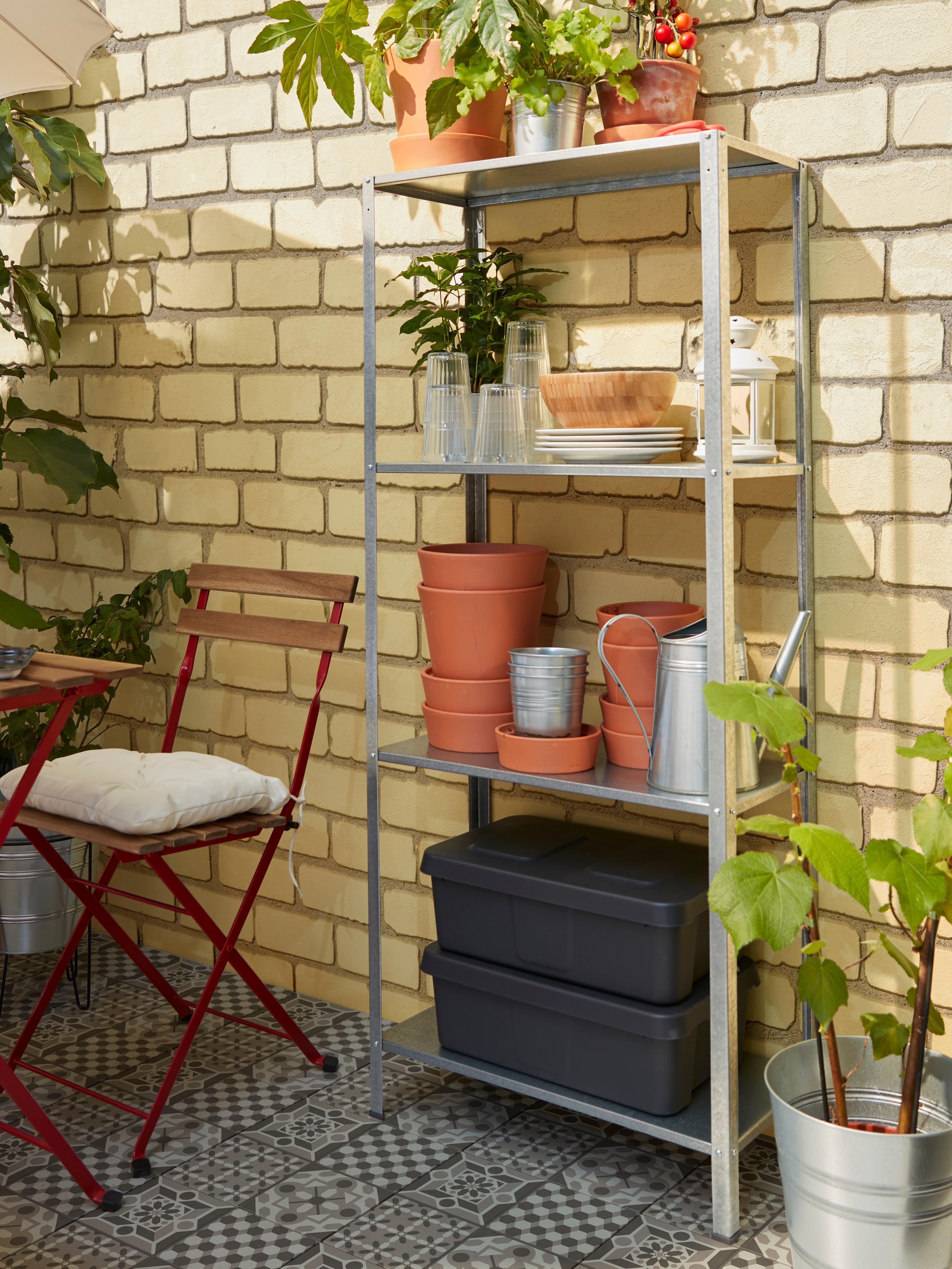 Scaffale a quattro ripiani con contenitori, vasi, piatti e bicchieri a portata di mano.