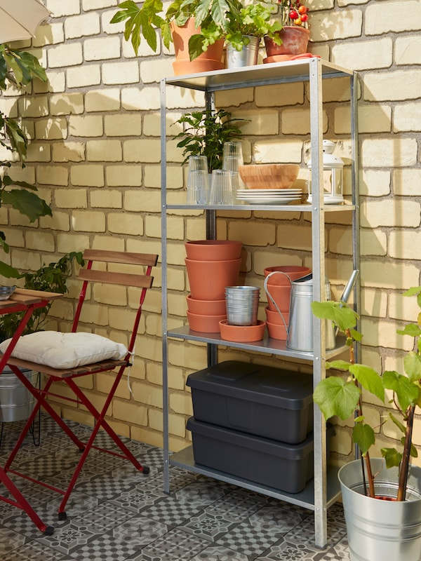A shelving unit with four shelves holding storage boxes, plant pots, plates and glasses.