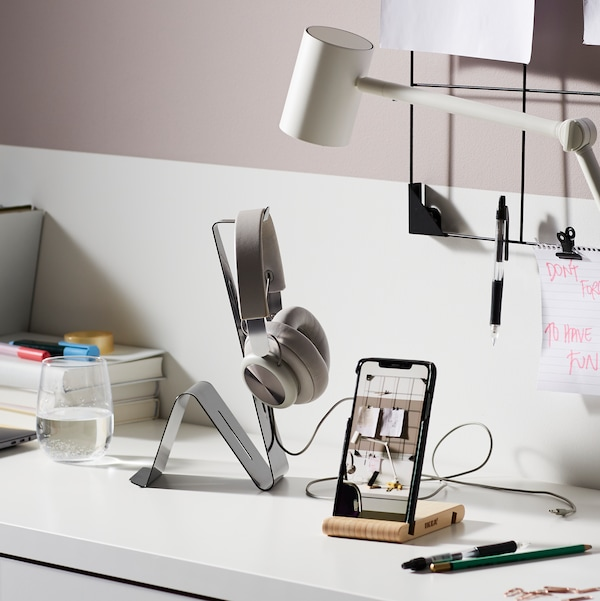 A MÖJLIGHET headset/tablet stand with headphones and a BERGENES holder for mobile/tablet with a mobile phone stand on a desk.