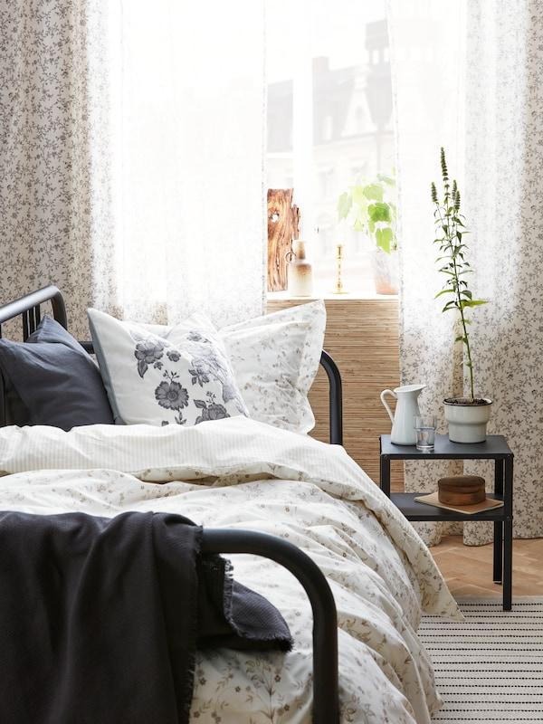 Une chambre illuminée aux couleurs neutres. Des linges de maison et des meubles noirs.
