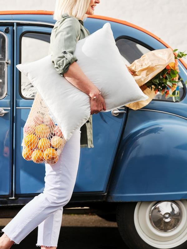 Eine Frau hält ihre Einkäufe und ein Kopfkissen im Arm.