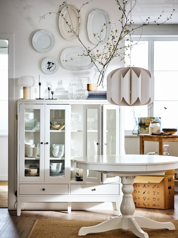 Une salle à manger blanche meublée d'une vitrine IDANÄS et d'une table INGATORP, une suspension MOJNA au-dessus d'elle.