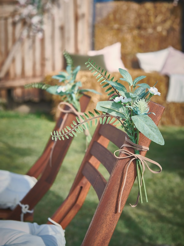 Sprigs of SMYCKYA leaves and flowers tied with beige ribbons decorate ÄPPLARÖ folding chairs at an outdoor party.