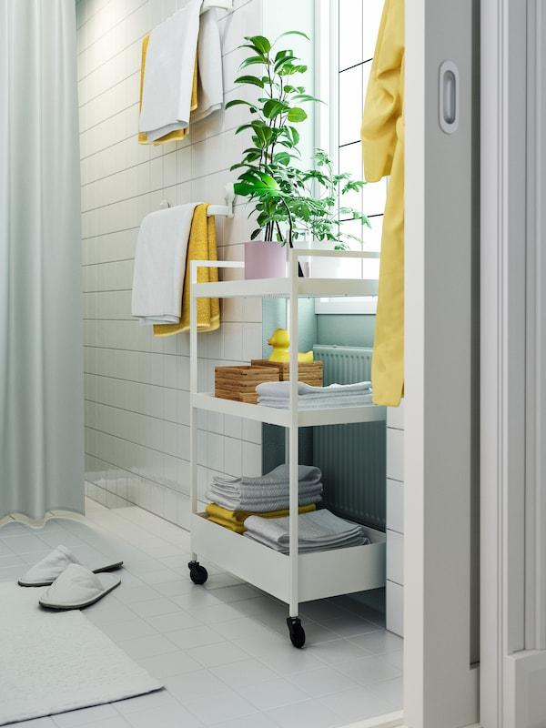 Kylpyhuone jossa on valkoinen NISSAFORS-tarjoiluvaunu, jonka hyllyillä on viikattuja pyyhkeitä sekä TAVELÅN-tarjotin.