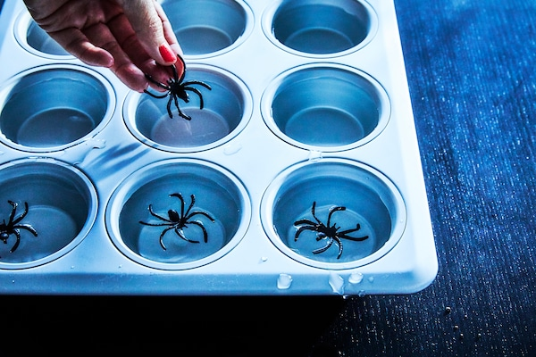 A silver muffin tin being filled with water and plastic spiders to make spider ice cubes as Halloween decorations
