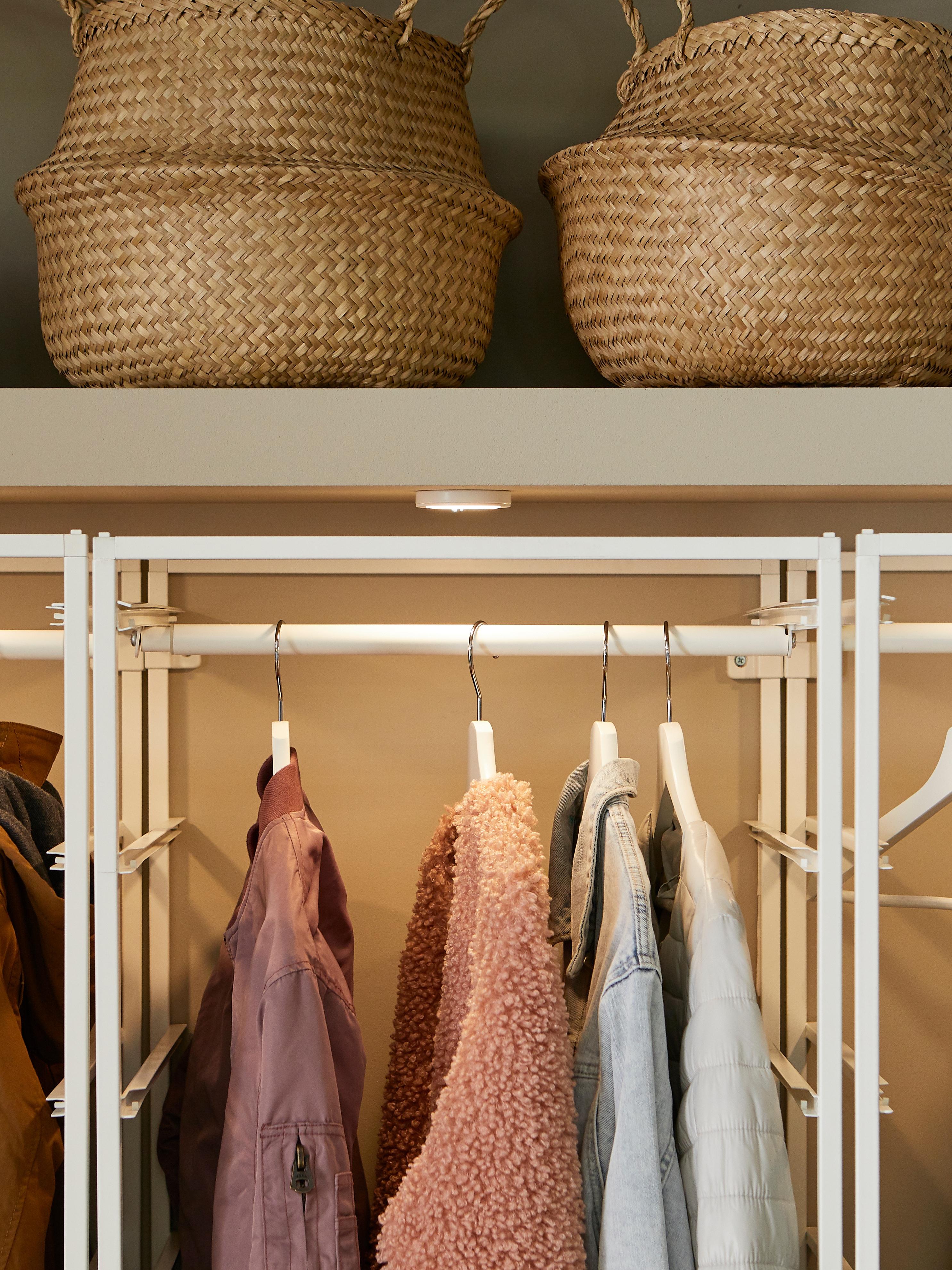 Kaputi koji vise na šipki za odjeću u otvorenoj jedinici za odlaganje ispod ugrađene police s okruglim, tankim VAXMYRA LED reflektorom.