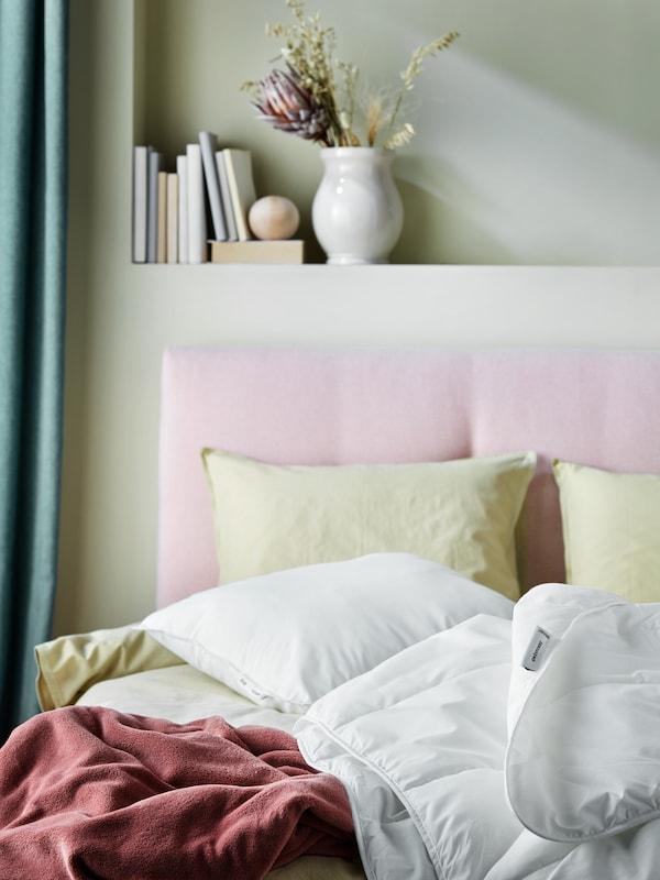 Vaalenpunaisen sängyn päällä on VILDKORN-tyyny, SMÅSPORRE-peitto, punainen TRATTVIVA-päiväpeitto ja keltaiset ÄNGSLILJA-vuodevaatteet