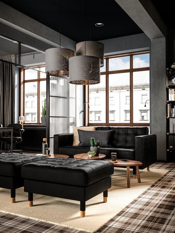 Area conversazione vicino alla finestra, con divano in pelle nera, tre grandi lampade a sospensione e tavolini in legno.