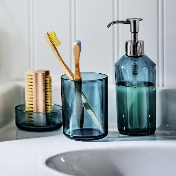 L'ensemble d'accessoires de bain 3 pièces SKISSEN sur le bord d'un lavabo, contenant une brosse à ongles, des brosses à dents et du savon liquide.