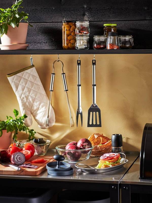 A GRILLSKÄR kitchen island loaded with barbecue accessories, including a stainless GRILLTIDER BBQ tray holding a hamburger.