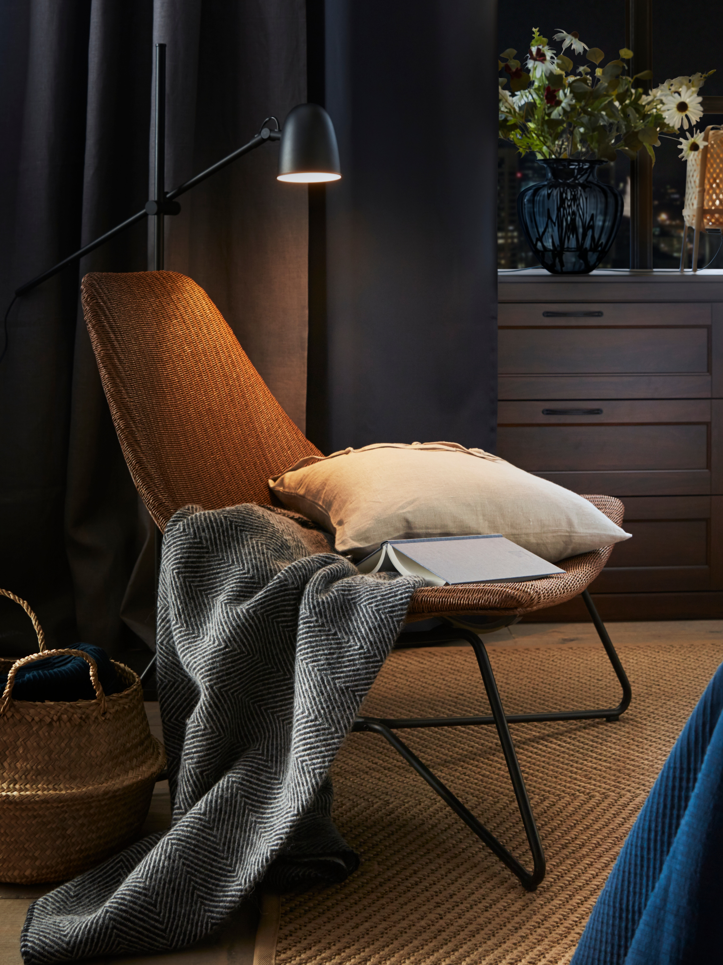 A scooped, dark brown/black RÅDVIKEN armchair that has a natural fibre seat and steel frame with a book, cushion and throw.