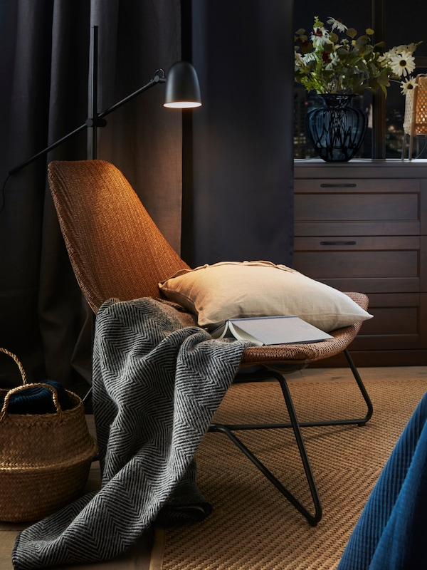 A pillow and a blanket are placed on a comfortable chair.