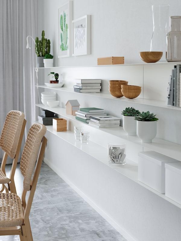 Minimalistiske, smale hvite hyller med treskåler, bøker, potteplanter, esker, ei hvit arbeidslampe og andre ting på en hvit vegg.