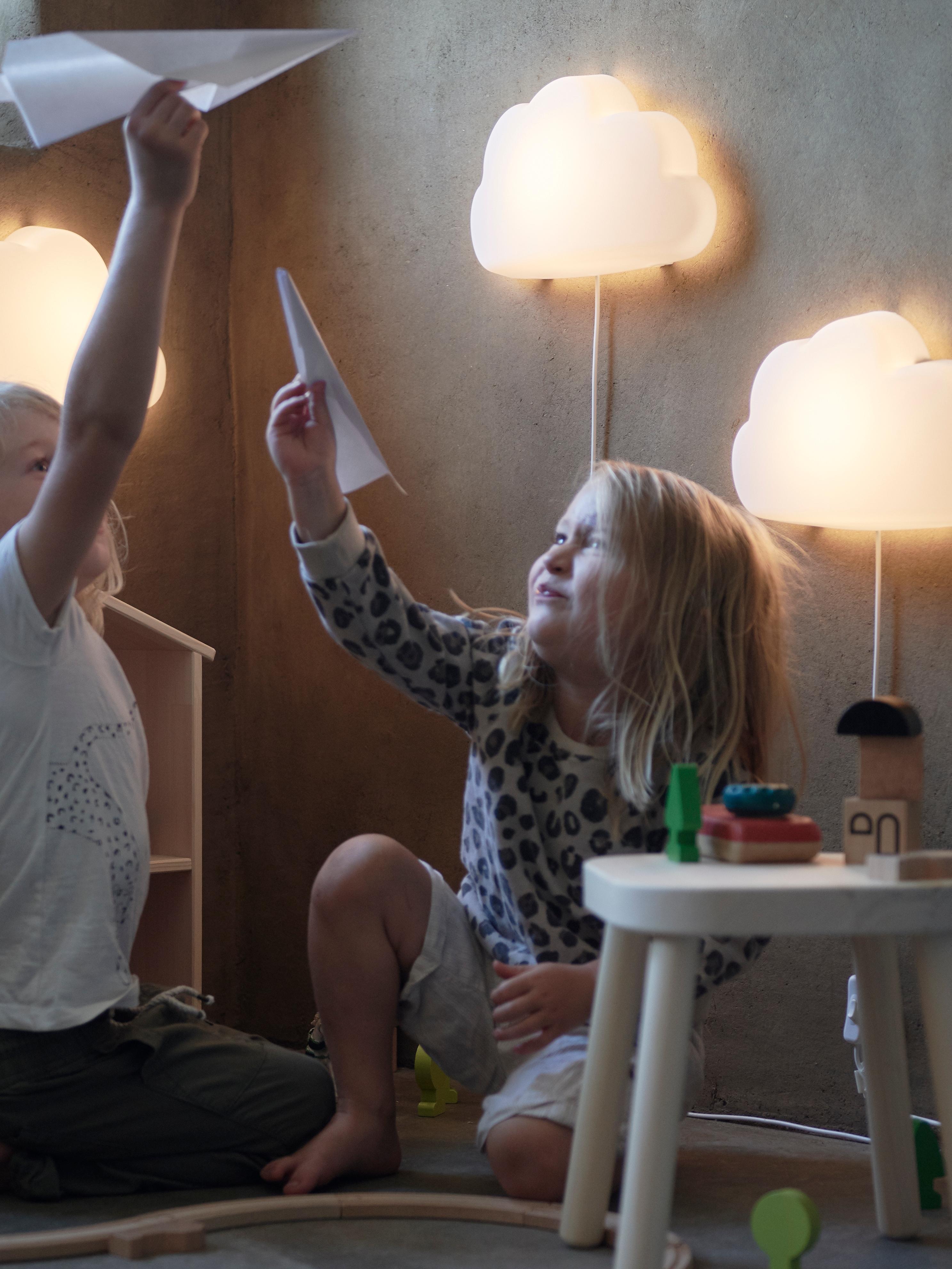 Due ragazze che giocano con aeroplani di carta davanti all'illuminazione a parete, accanto a uno sgabello di legno bianco con sopra dei giocattoli.