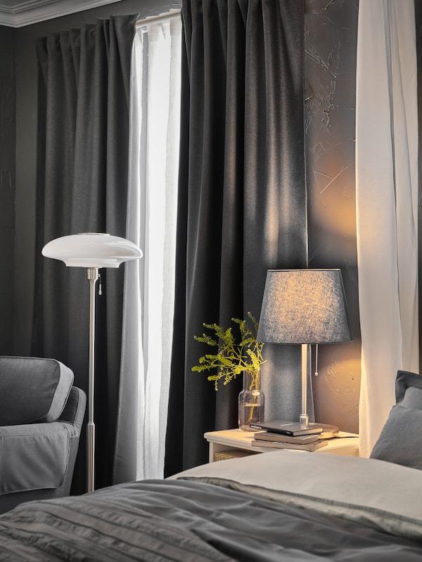 Postel s šedým ložním prádlem, bílým nočním stolkem s šedou stolní lampou a bílou stojací lampou, a šedými závěsy na oknech.