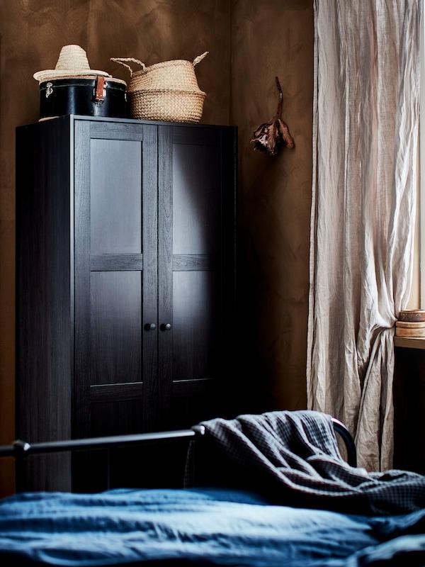 Cortines beix i un armari RAKKESTAD de color negre marró amb cistelles a la part superior, al costat dels peus d'un llit amb roba blava.