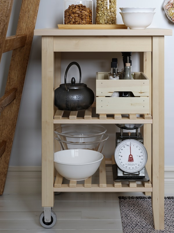 A BEKVÄM birch kitchen cart with an OSTBIT bamboo tray, bowls and two jars on top, and scales, a teapot and a box below.
