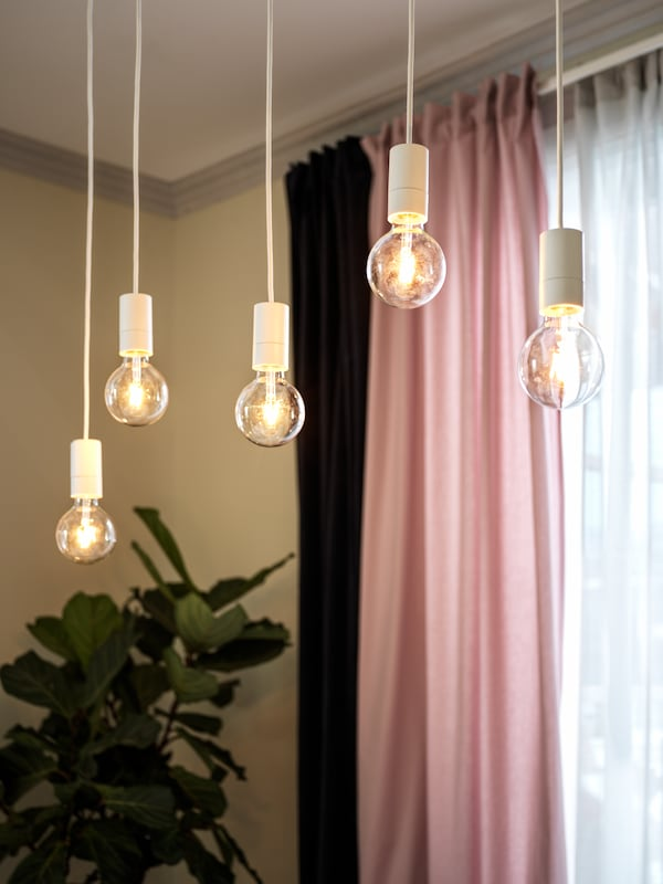 A row of LUNNOM lit bulbs hanging at different heights in white SUNNEBY cords in front of light-pink KALKFLY curtains.