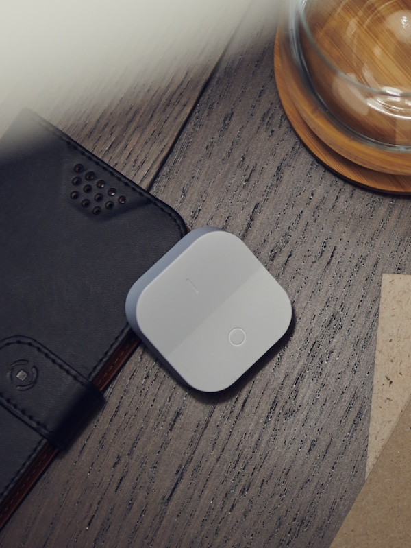 A white TRÅDFRI wireless dimmer lies on a wooden floor partially on top of a mobile phone in a wallet case.