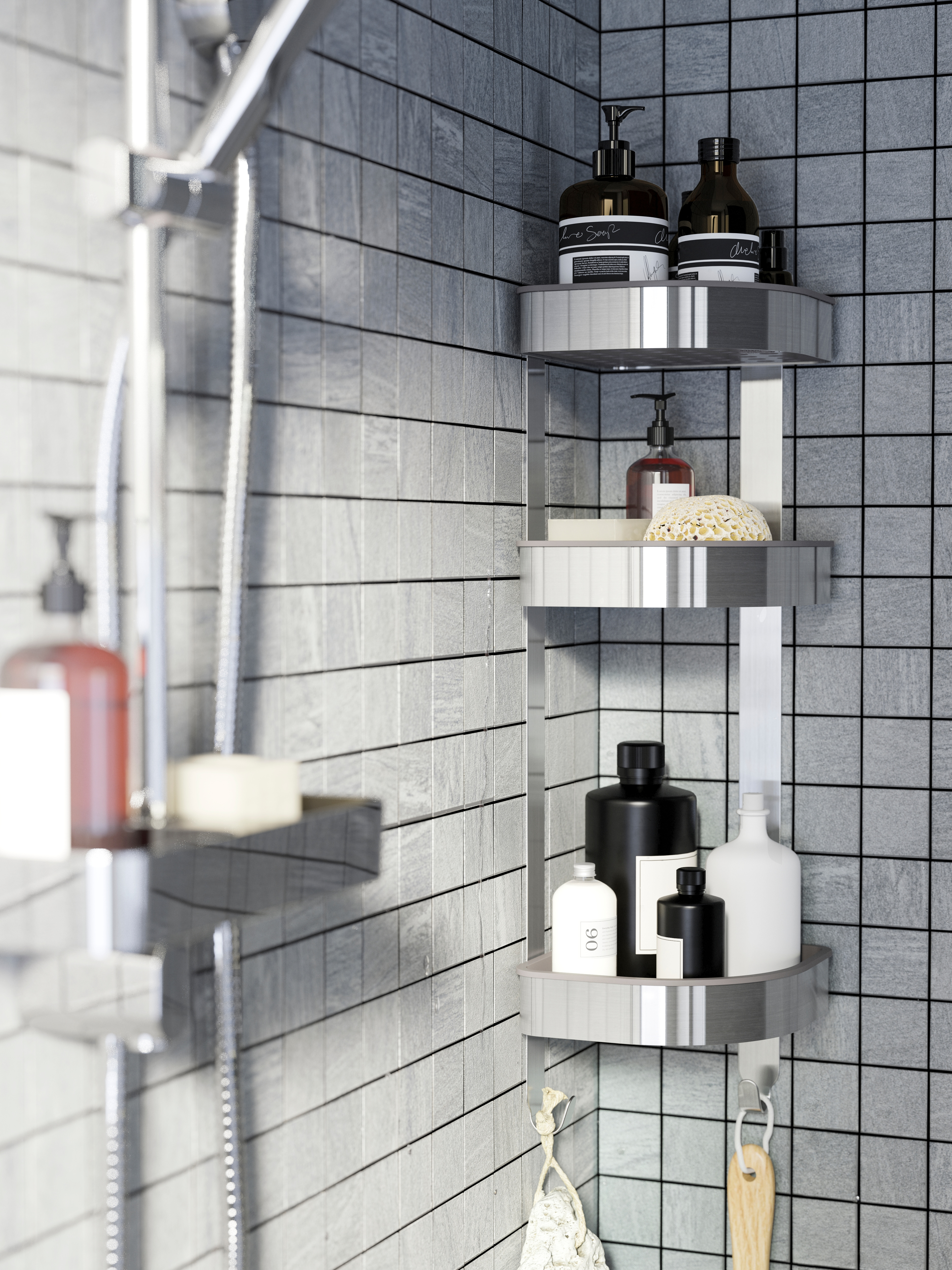A grey tiled shower with a stainless steel BROGRUND corner wall shelf that has two hooks and bottles on its three shelves.
