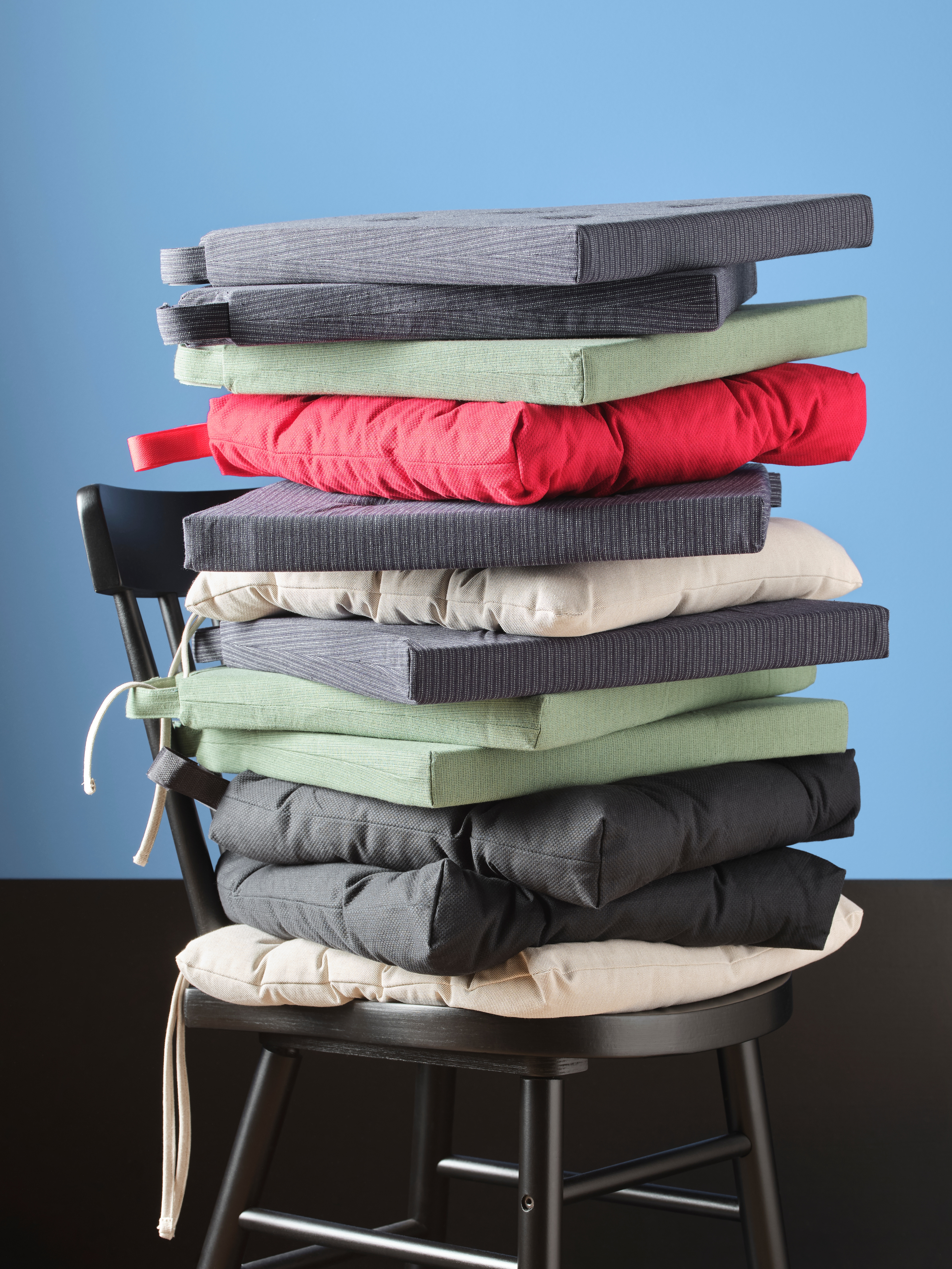 A dining chair holds a stack of chair pads in diverse colours and shapes, including a dark blue/striped JUSTINA chair pad.