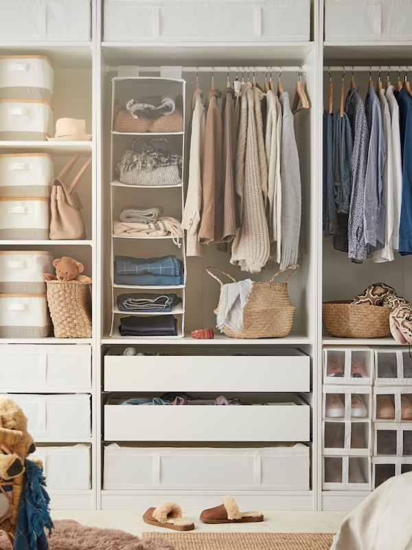 A large, open wardrobe with clothes hanging from rails, shoes in shoe boxes, drawers, SKUBB storage cases, baskets and boxes.