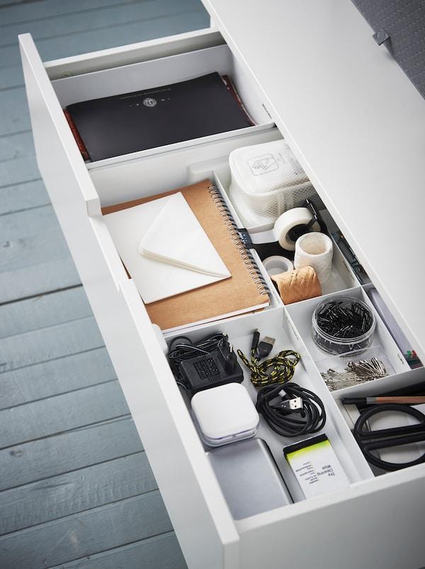 Valkoinen lipasto, jonka yksi laatikko on auki. Laatikossa näkyy erilaisia toimistotarvikkeita KUGGIS-lokerikossa.