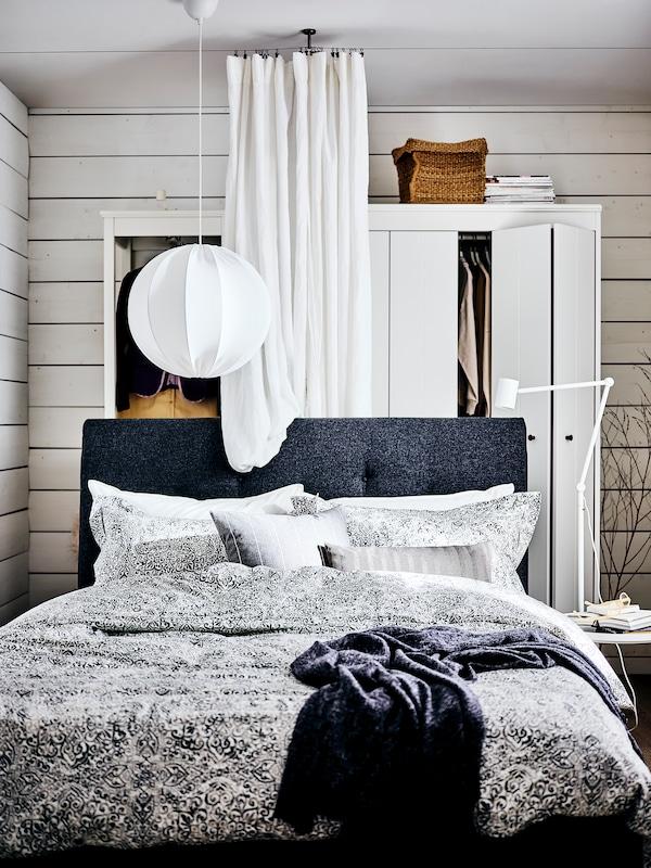 Una cama IDANÄS Gunnared acolchada en gris oscuro, ropa de cama ÄNGSKLOCKA con un patrón floral blanco / gris.  Un armario IDANÄS blanco detrás de la cortina blanca DYTÅG.