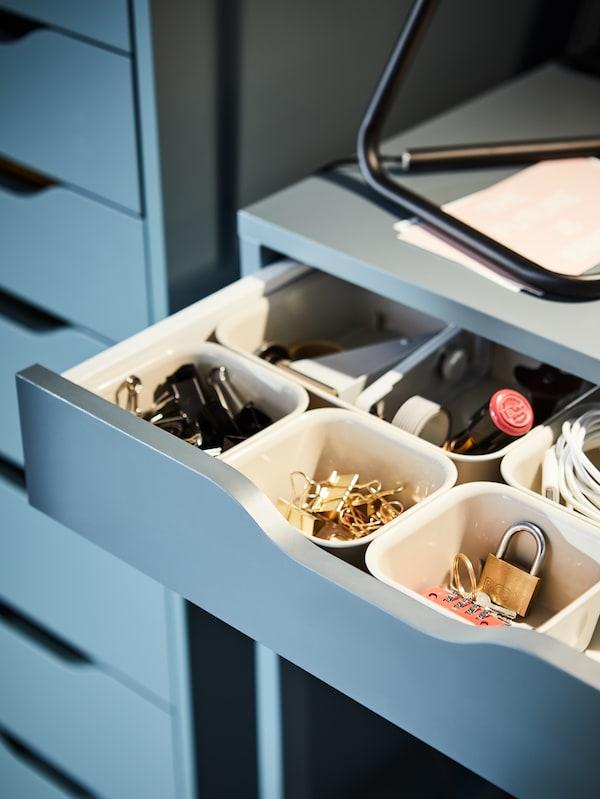 Organiseurs NOJIG remplis de fournitures de bureau dans un tiroir du bureau ALEX en finition gris-turquoise.