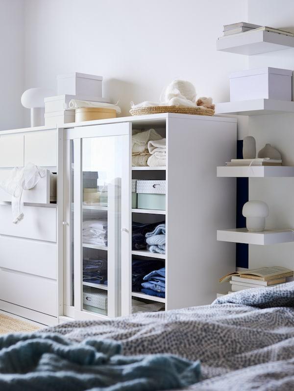 Bilik tidur kecil yang mempunyai almari 6 laci MALM berwarna putih, kabinet SYVDE berwarna putith dengan pintu kaca dan unit para dinding LACK berwarna putih.