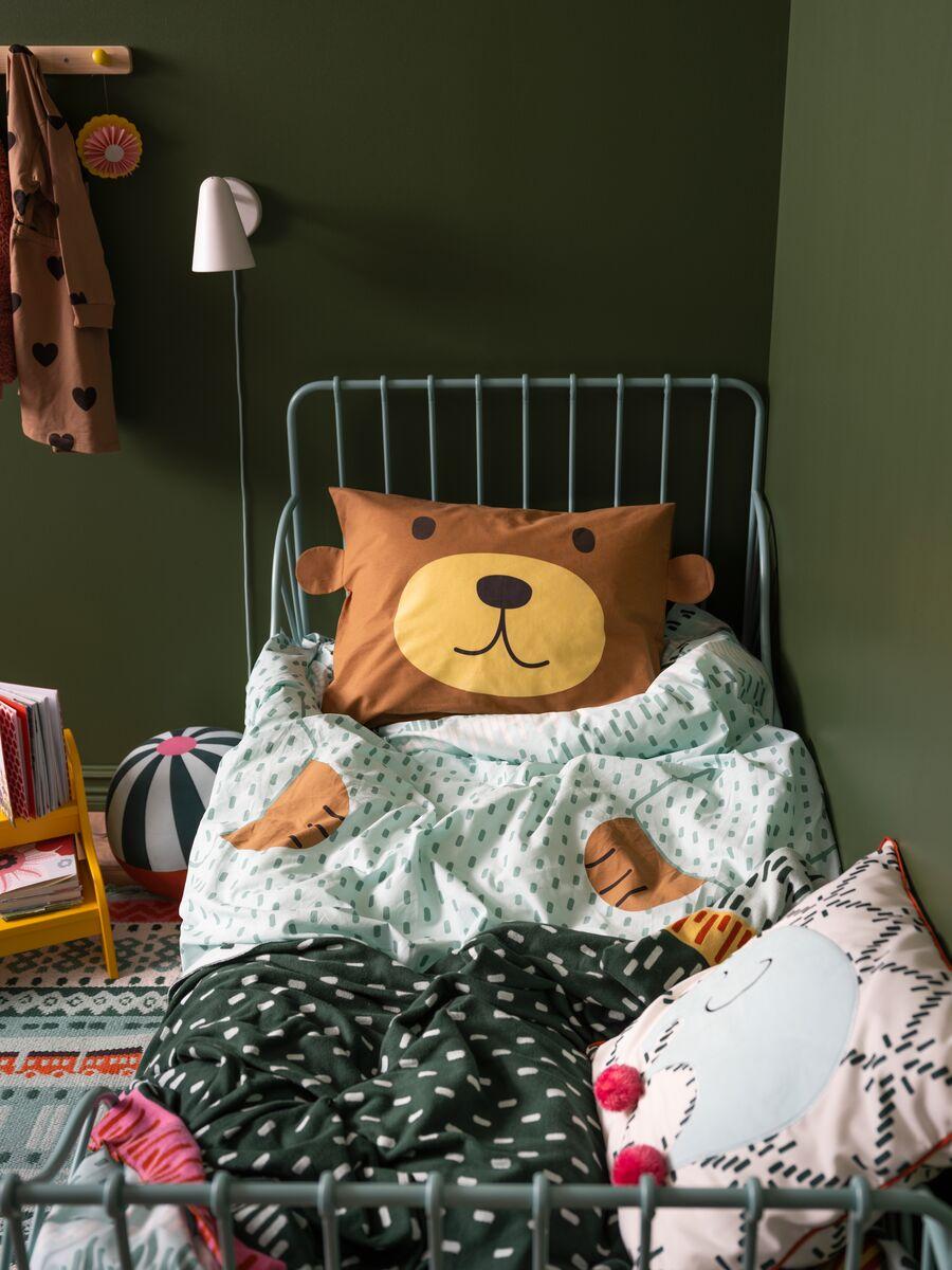 Dječji kovani željezni krevet s KÄPPHÄST posteljinom s uzorkom medvjeda i ukrasni jastuk, s loptom i stalkom za knjige na tepihu.