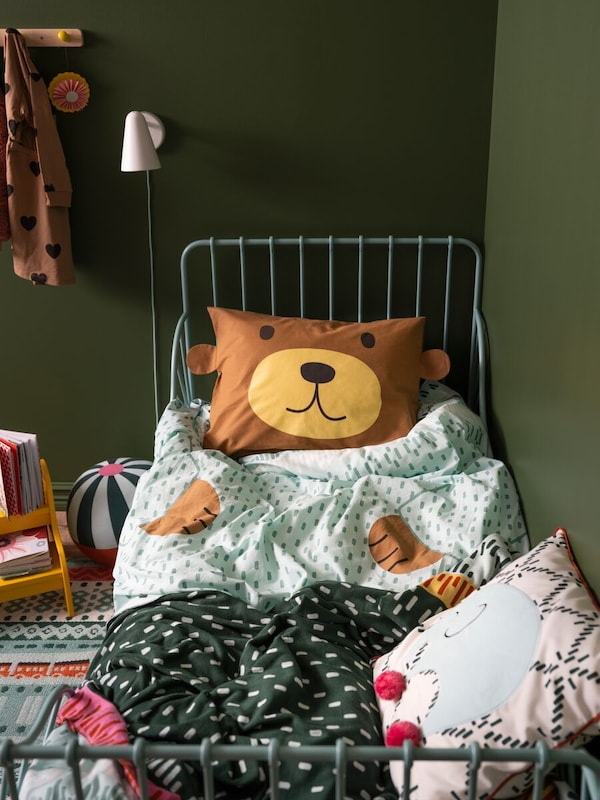 A rumpled twin bed dressed with assorted bed linens, including a pillow printed with a friendly bear's face.