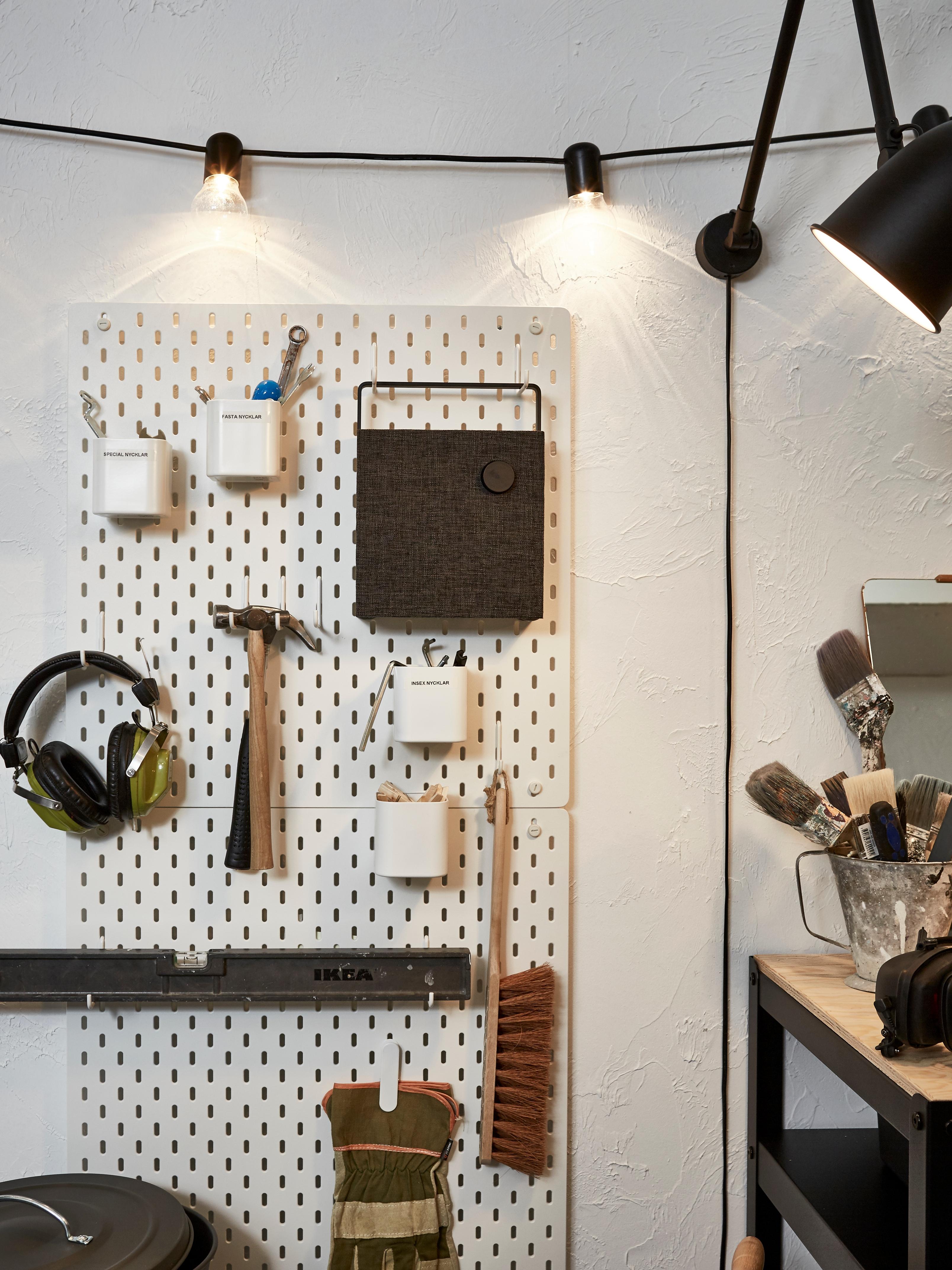 Zid garaže s dvije bijele SKÅDIS rupičaste ploče koje drže alate i zvučnik na kuki ispod rasvjetnog lanca pored radne ploče.