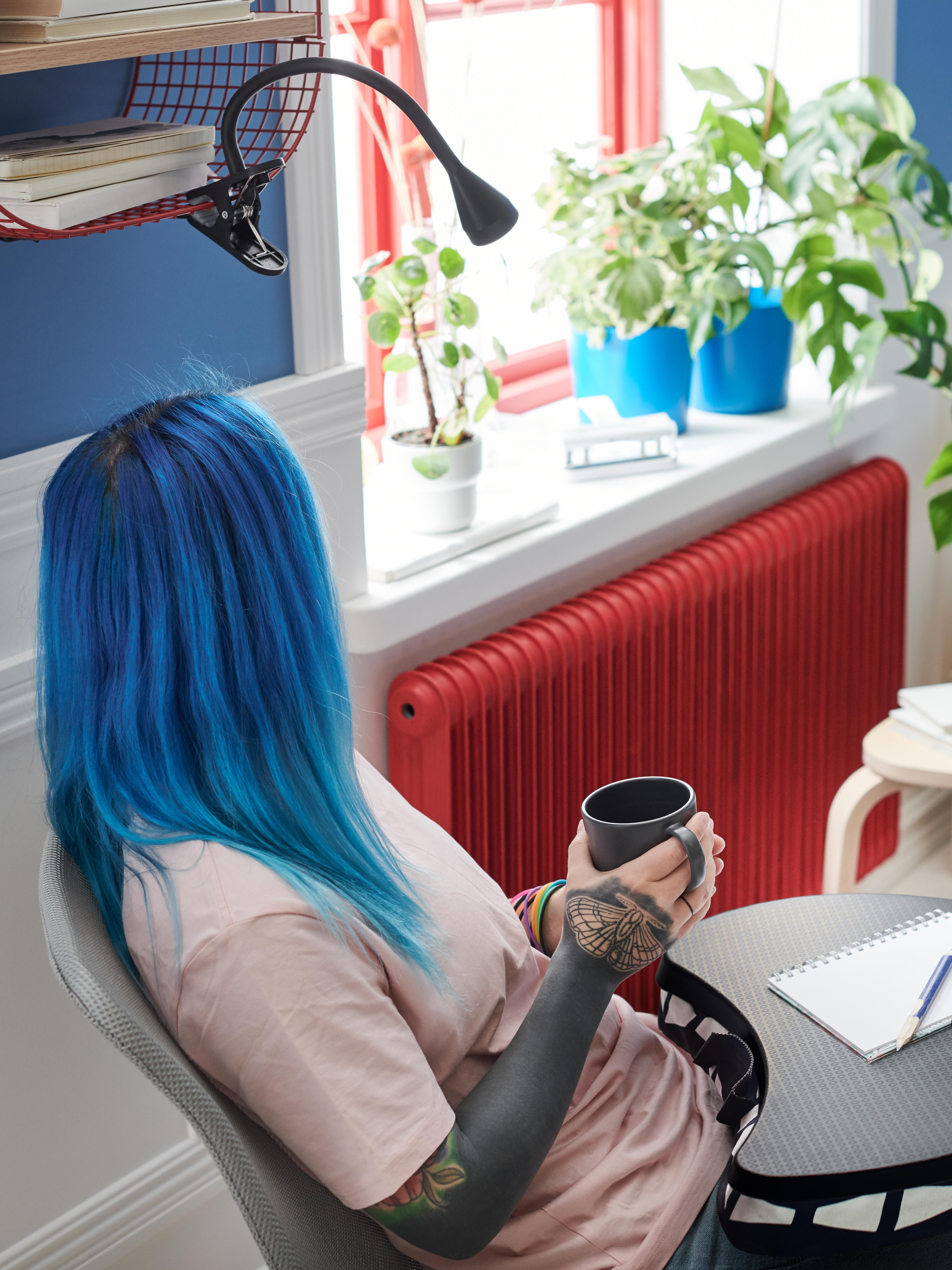 Žena sjedi naslonjena u stolicu držeći DINERA šalicu, u krilu ima BYLLAN držač za laptop i bilježnicu.