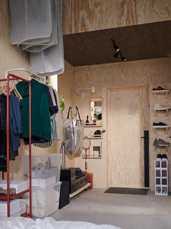 Liten hall med höga väggar, klädstång och konsoler monteras vertikalt för att skapa plats för kläder och skor.