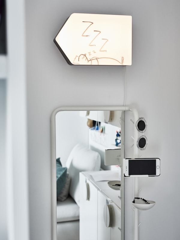 A lit wall lamp shaped like an arrow with a drawing of a sleeping person hangs above a full-length mirror.