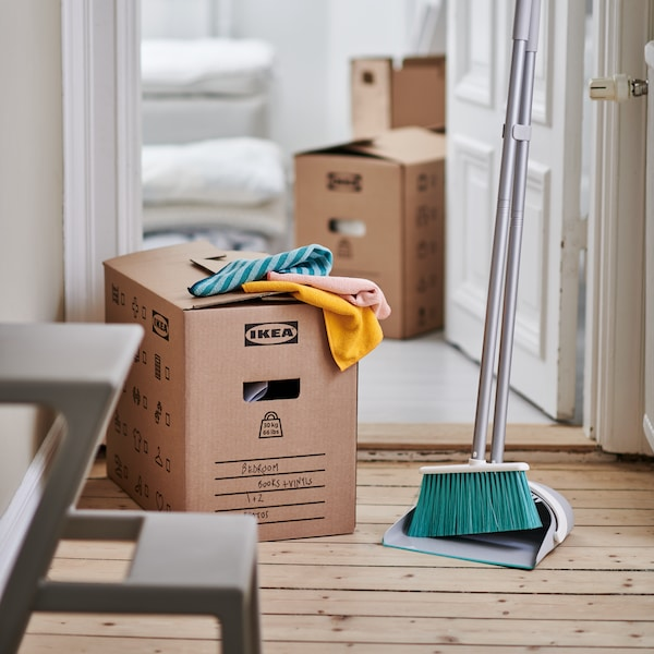 Several cleaning cloths placed on a cardboard box, next to a broom with pan.