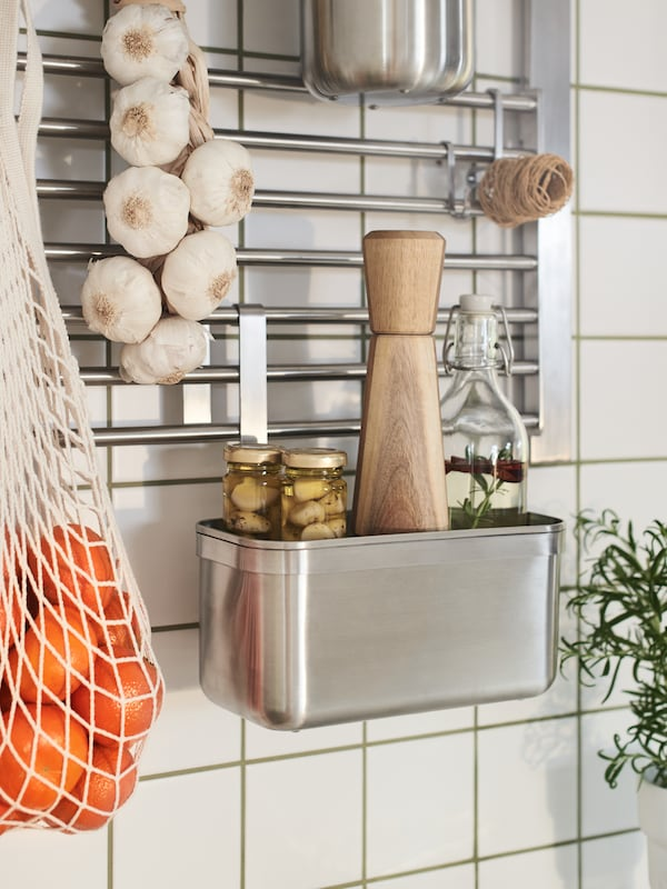 A kitchen wall with KUNGSFORS containers and hooks hanging on a wall grid, all in stainless steel, holding jars and garlic.