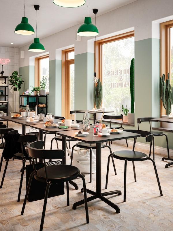 Quattro tavoli color antracite disposti a formare una lunga tavolata, caffè e brioche, sedie e lampade a sospensione verde scuro.