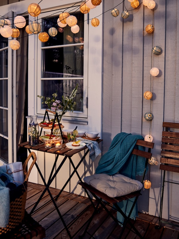C'est le coucher du soleil et les lumières sont faibles mais on peut voir une petite table d'extérieur avec deux chaises sur un balcon, entourée de lampes solaires allumées.