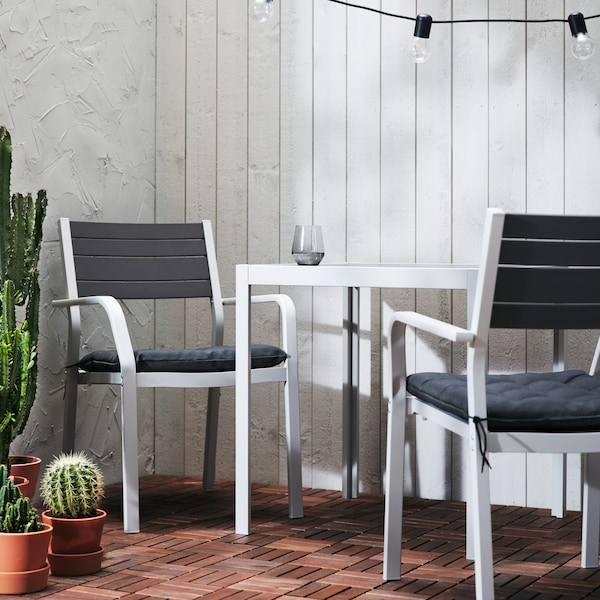 An outdoor table in white, with two chairs in white with dark gray upholstery and potted plants of different types.