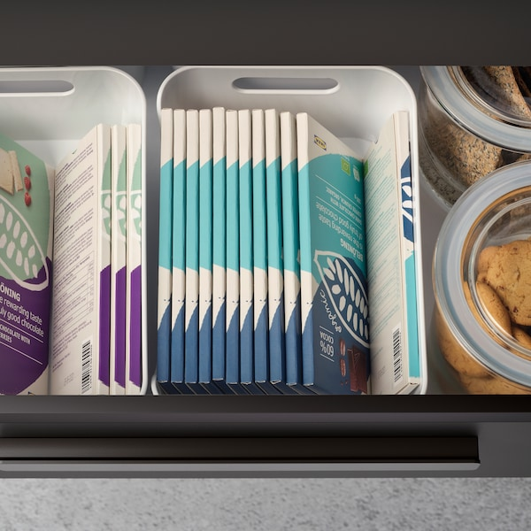 A pulled-out kitchen drawer revealing BELÖNING chocolate bars neatly stacked inside VARIERA boxes and two glass jars.