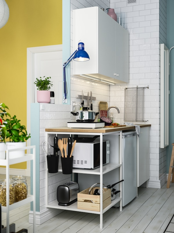 A white ENHET kitchen combination in an odd corner with a small refrigerator, portable induction hob and microwave oven.