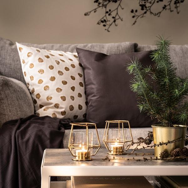 1 weisser Polster mit goldenen Flecken neben einem anthrazitfarbenem Polster auf einer Couch, davor ein Tisch mit Kerzen