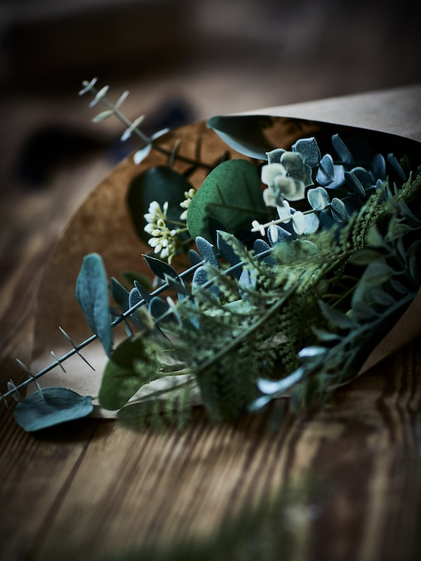 An indoor-outdoor, green SMYCKA artificial bouquet wrapped in natural-colour paper and placed on a wooden surface.