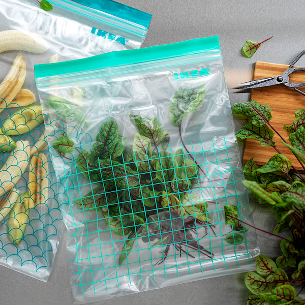 Two sizes of ISTAD plastic bags with blue and turquoise details filled with various herbs and food, on top of a worktop.
