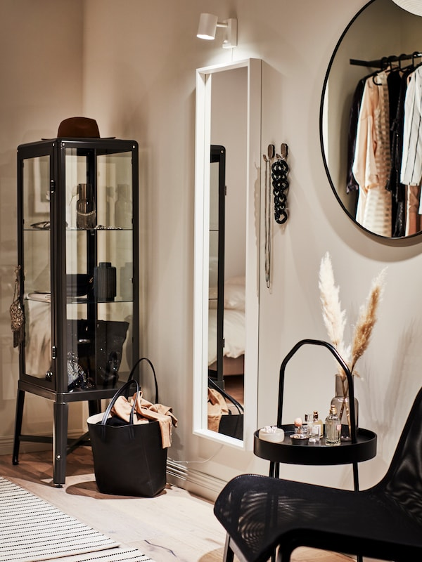 A stylish dressing area with a dark grey FABRIKÖR glass-door cabinet and a white NISSEDAL mirror and NYMÅNE lamp on the wall.